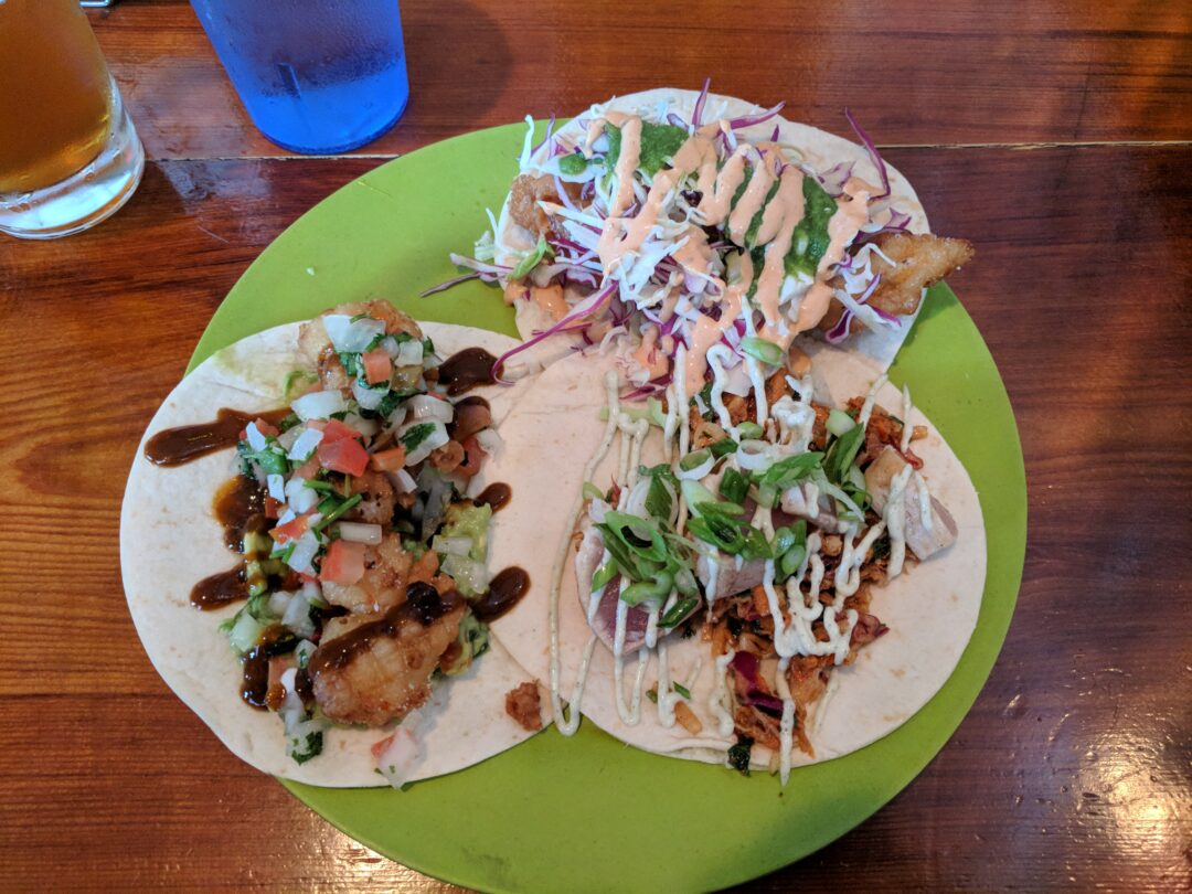A plate with 3 different types of fish tacos.