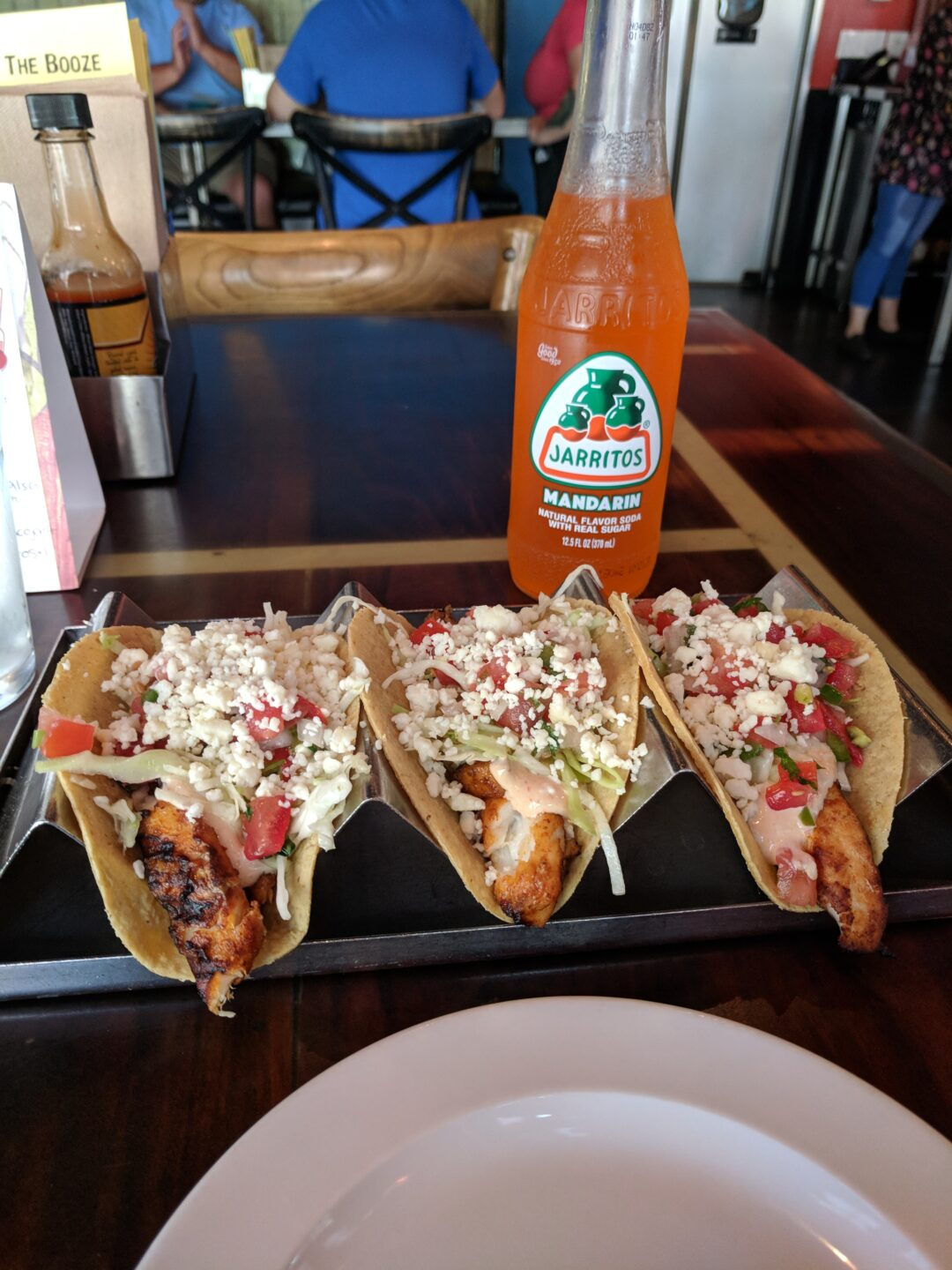 Grilled fish tacos and mandarin Jarritos soda in a bottle.