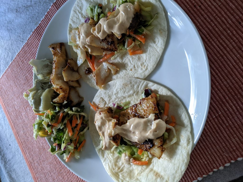 Two pan fried cod fish tacos on a plate with coleslaw, artichokes, and extra fish.