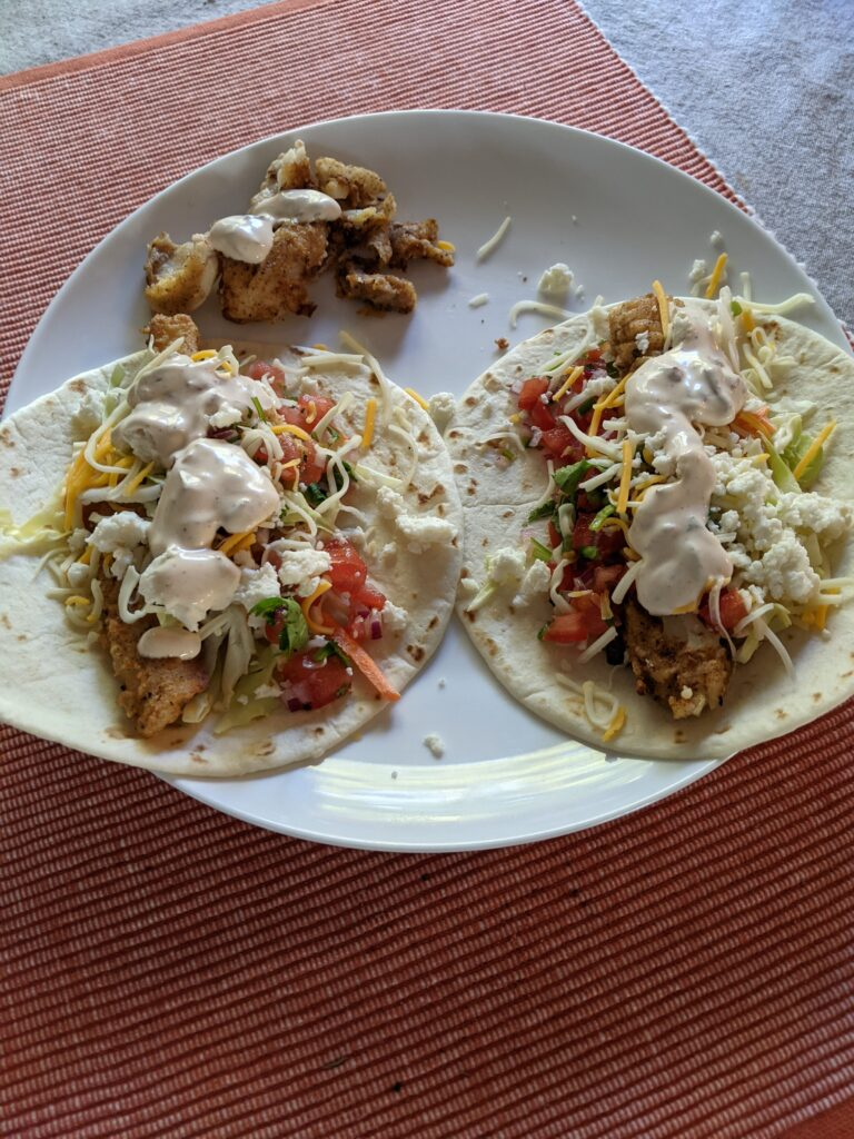 A plate with two very delicious fish tacos.